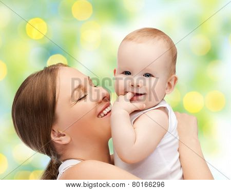 people, family, motherhood and children concept - happy mother hugging adorable baby with finger in his mouth over green lights background