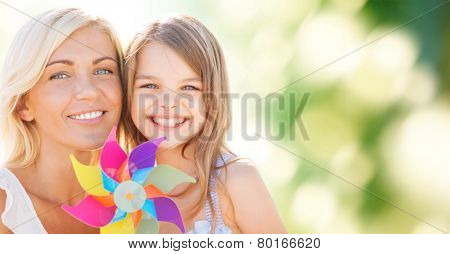summer holidays, family, children and people concept - happy mother and girl with pinwheel toy over green background