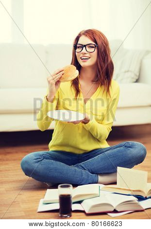 education and home concept - smiling student eating hamburger and doing homework at home