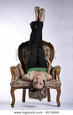 Beautiful young woman upside down on a chair
