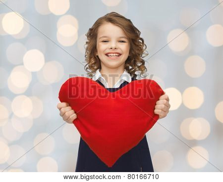 love, charity, holidays, children and people concept - smiling little school girl with red heart over lights background
