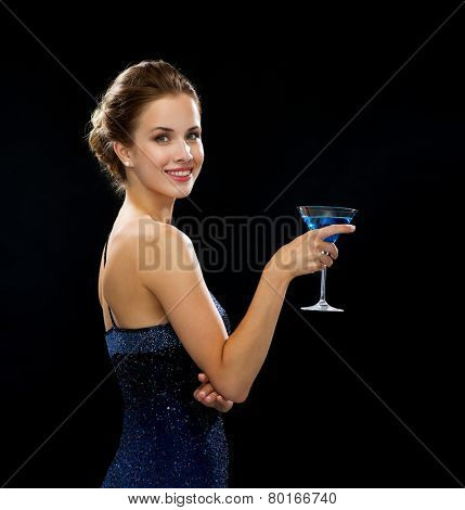 party, drinks, holidays, luxury and celebration concept - smiling woman in evening dress holding cocktail over black background