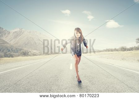 Young businesswoman in suit running on road