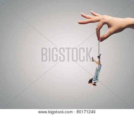 Giant human hand holding miniature of businesswoman