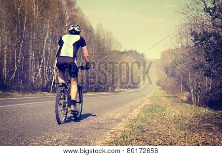 Sporty Man Riding a Bicycle on the Road