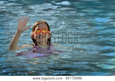 Portrait of young girl swimming with orange swim goggles in pool