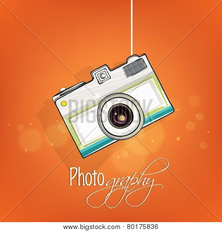 Creative photographic camera hanging on shiny orange background.