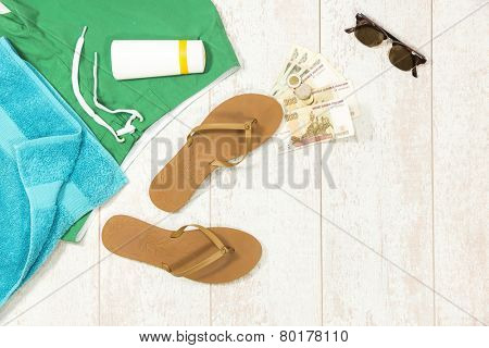 Background with beach supplies and foreign currency money on floorboard