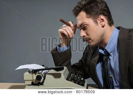Author smoking cigar at typewriter