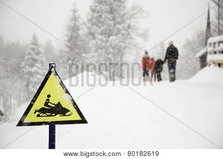 Frozen snowmobile sign and fogy, snowy background with walking family