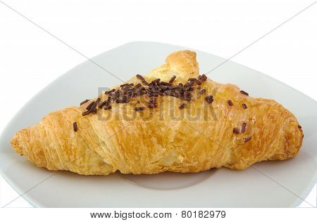 Croissant with chocolate on bright background.