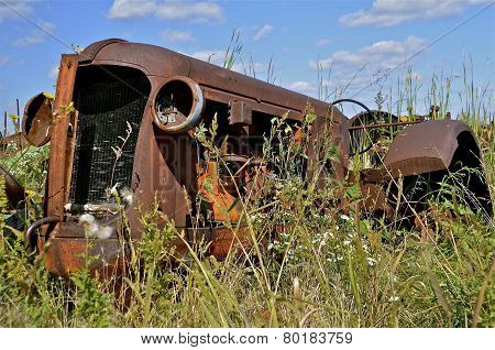 Frame of a n old rusty tractor surrounded by weeds