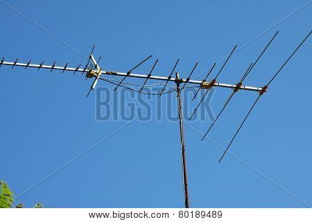 Old TV antenna on house roof with bule sky