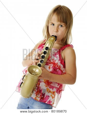 An attractive young elementary girl playing a large, toy sax.  On a white background.
