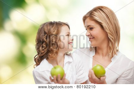 people, family, healthy eating and parenting concept - happy mother and daughter with apples over green background