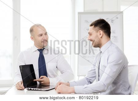 business, technology and office concept - two smiling businessmen with laptop having presentation in office