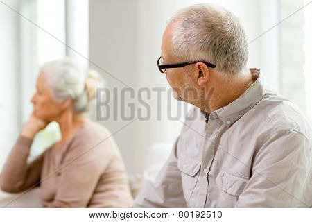 family, relations, age and people concept - senior couple sitting on sofa at home