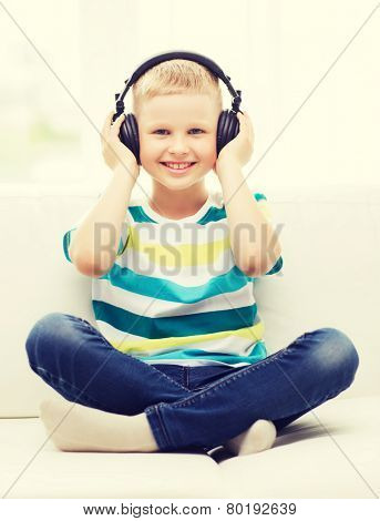 home, leisure, new technology, childhood and music concept - smiling little boy with headphones at home