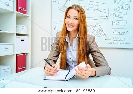 Young businesswoman ponders something sitting in the office.