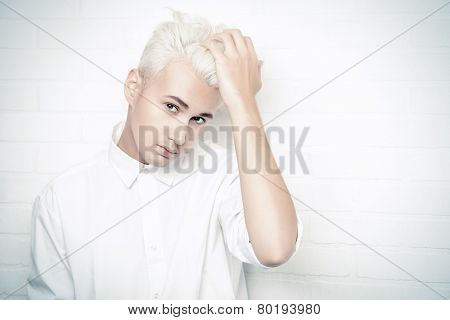 Beautiful young man with sensual look posing at studio by the white brick wall. Hairstyle, fashion.