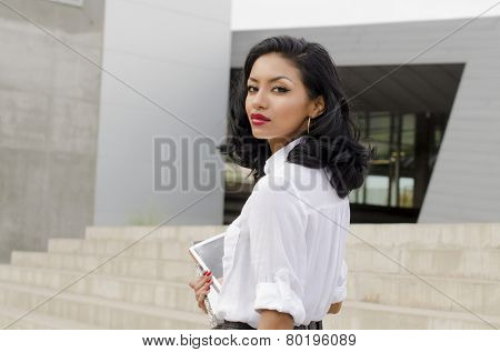 Outdoor photo of  young woman walking carrying books turning head