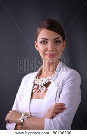 Portrait of young woman with beads, isolated on grey background