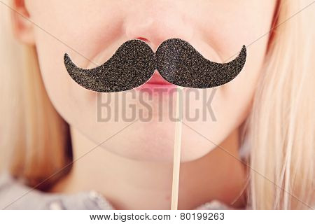 Woman Holding Mustache On A Stick In Front Of Her Face