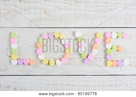 The word LOVE spelled out using pastel candy Valentine's hearts. Overhead shot on a rustic whitewashed wood table with copy space.