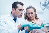 picture of prosthesis  - Male dentist showing woman prosthesis teeth in the dentists chair - JPG