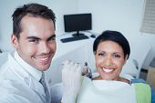 picture of dentist  - Male dentist examining womans teeth in the dentists chair - JPG