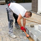 image of paving stone  - Construction worker placing concrete paving stones to build up a pavement and a terrace in front of a house - JPG