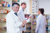 pic of prescription  - Smiling pharmacist in lab coat writing a prescription in the pharmacy - JPG