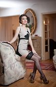 image of tight dress  - Happy smiling attractive woman wearing an elegant dress and black stockings sitting on the sofa arm - JPG