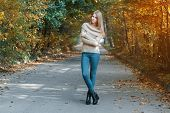 image of pullovers  - Pretty girl in a pullover standing in autumn park - JPG
