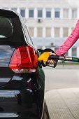 pic of petrol  - Woman filling up car at petrol station black car  - JPG