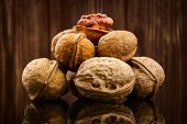 stock photo of walnut  - Walnut kernels and whole walnuts on rustic old wooden background