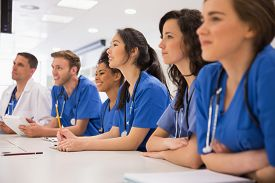 stock photo of half  - Medical students listening sitting at desk at the university - JPG