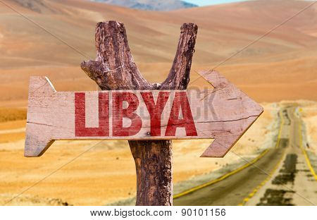 Libya wooden sign with desert road background