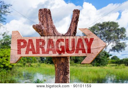 Paraguay wooden sign with countryside background