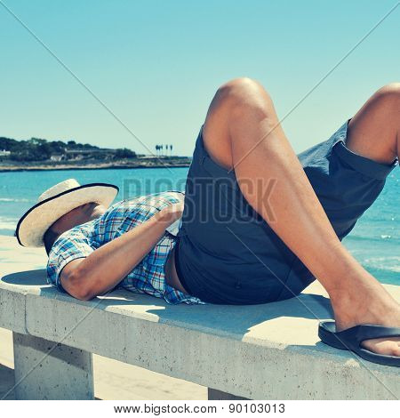 a young caucasian man with a straw hat on his face lying down in a street bench near the sea