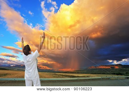Giant cloud illuminated by the sunset. Yoga on the road. Elderly woman in white performs asana
