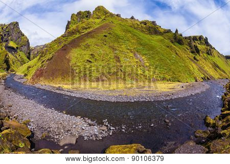 The canyon Pakgil is located among fantastic rocks. On bottom of canyon  fast shallow stream flows. The summer blossoming Iceland. The photo was taken Fisheye lens