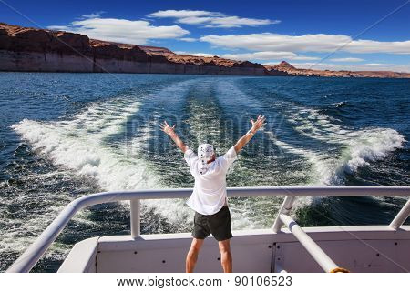 Man in  white shirt on the stern boat fascinated by nature. The lake is surrounded by picturesque beaches of the orange sandstone. Artificial lake Powell on the Colorado River, USA