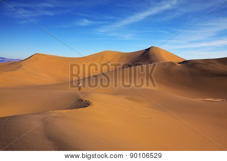Sunrise in the orange sands of the desert Mesquite Flat, USA. Middle-aged woman - photographer in a striped T-shirt is among the sand dunes
