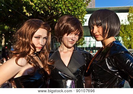 Three Girls In Black In Costumes  Are Posing For Photografers