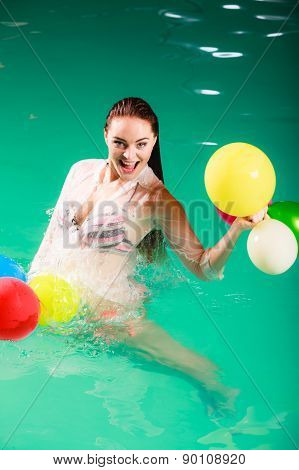 Woman Having Fun With Baloons In Water.