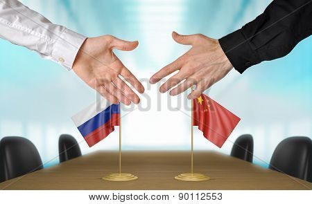 Russia and China diplomats agreeing on a deal