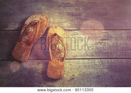 Vacation Concept. Pair of beach sandals on wood background
