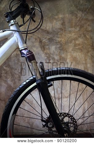 Close Up Front Wheel Tire Of Mountain Bike Against Grungy Cement Wall Use For Bicycle And Biking Con