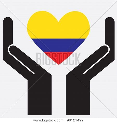 Hand showing Colombia flag in a heart shape.